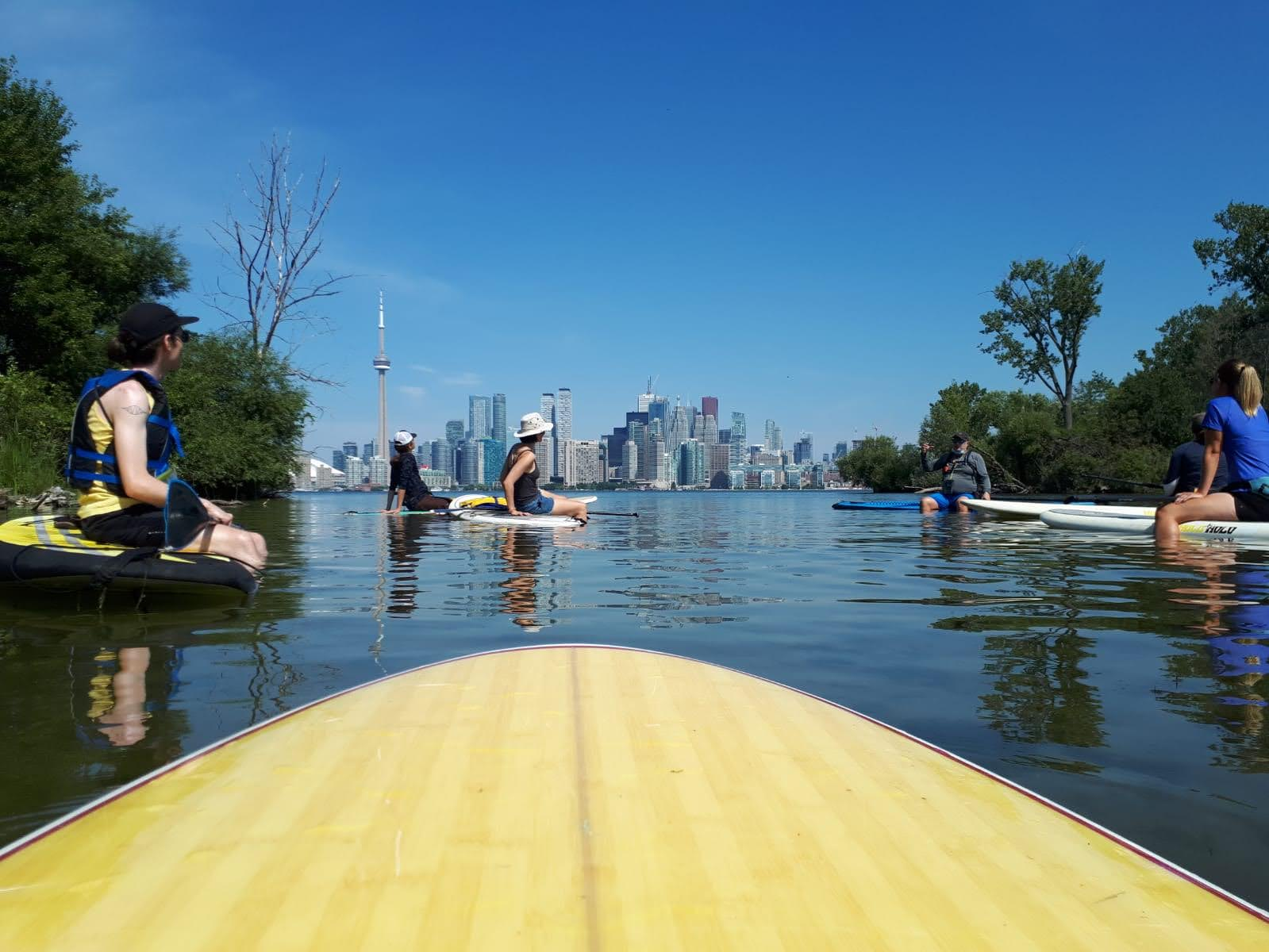 paddle boarders with the Toronto skyline in the background